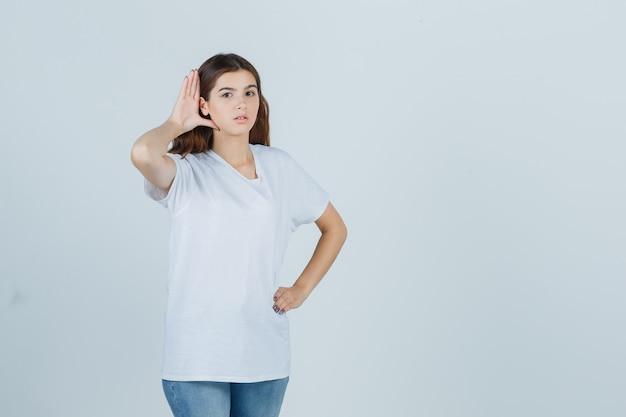 Jong meisje dat in wit t-shirt privégesprek afluistert en nieuwsgierig, vooraanzicht kijkt.