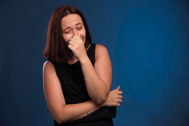 Jong meisje dat in zwart overhemd zijn adem houdt.