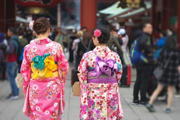 Jong meisje dat japanse kimono draagt die zich voor sensoji-tempel in tokyo bevindt