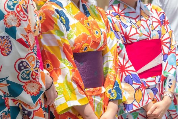 Jong meisje dat japanse kimono draagt die zich voor sensoji-tempel in tokyo, japan bevindt.