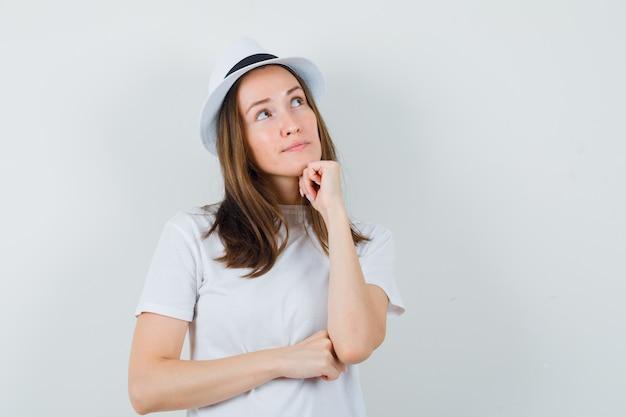 Jong meisje dat kin op vuist in wit t-shirt, hoed steunt en dromerig kijkt. vooraanzicht.