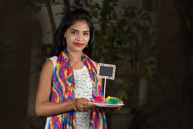 Jong meisje dat klein bord en poederkleur houdt ter gelegenheid van holi-festival.