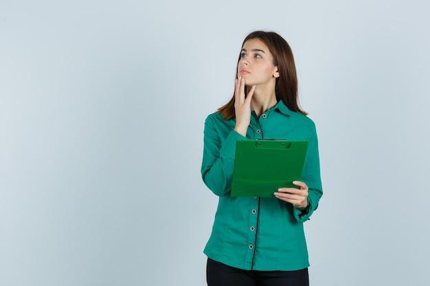 Jong meisje dat klembord bekijkt, hand op kin zet in groene blouse, zwarte broek en peinzend, vooraanzicht kijkt.