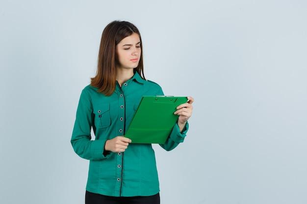 Jong meisje dat klembord in groene blouse, zwarte broek bekijkt en verward, vooraanzicht kijkt.