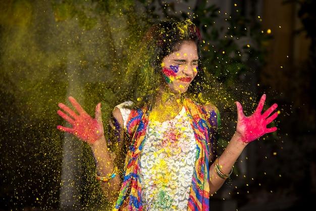 Jong meisje dat kleurrijke palm toont en holi met kleurenplons viert
