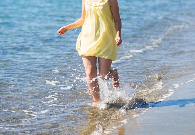 Jong meisje dat langs het strand van een overzeese close-up loopt