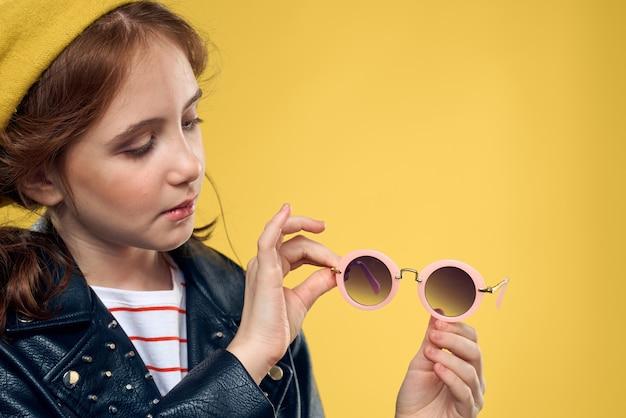 Jong meisje dat leerjasje op gele achtergrond draagt
