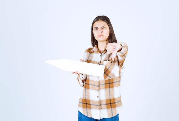 Jong meisje dat lege toespraakpijlaanwijzer houdt en duimen naar beneden geeft.