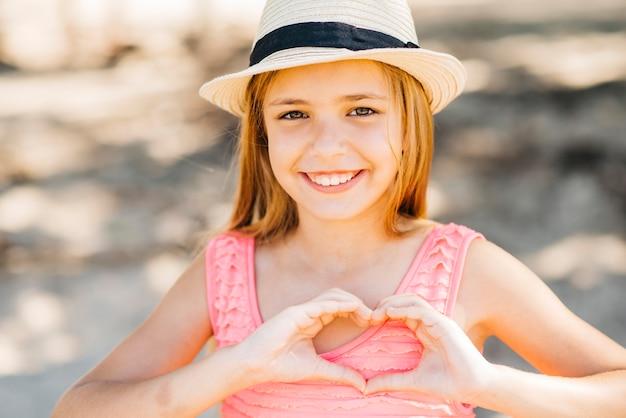 Jong meisje dat liefdegebaar toont en camera op strand bekijkt