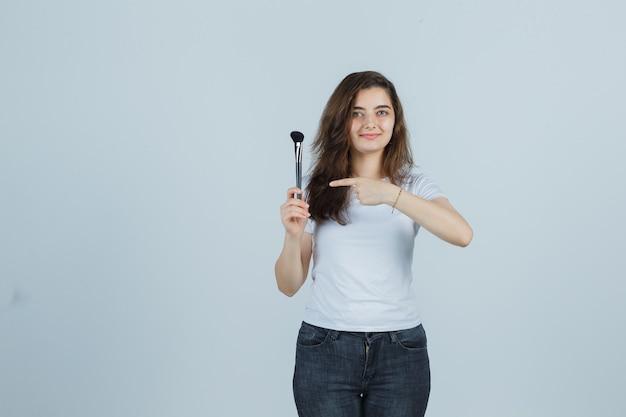 Jong meisje dat make-upborstel in t-shirt, jeans richt en zelfverzekerd, vooraanzicht kijkt.