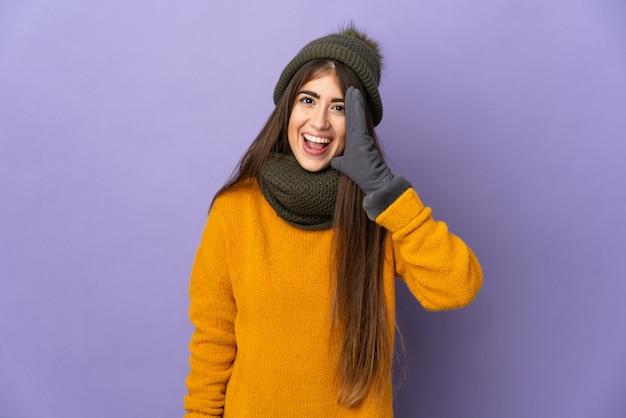 Jong meisje dat met de winterhoed op purpere muur wordt geïsoleerd die met wijd open mond schreeuwt