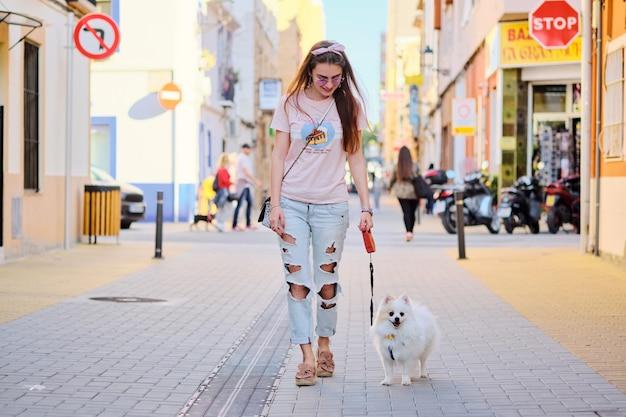 Jong meisje dat met een witte pluizige pomeranian loopt.