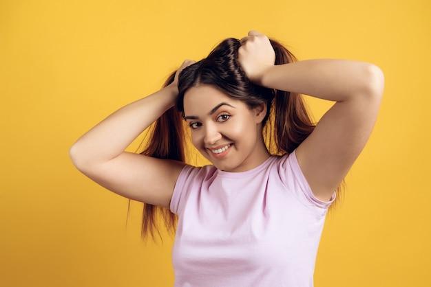 Jong meisje dat met haar handen op haar hoofd glimlacht