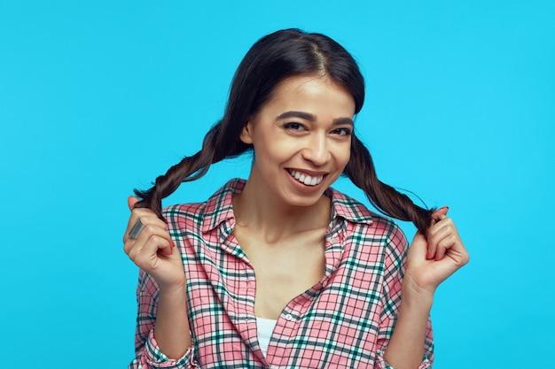 Jong meisje dat met heldere glimlach met haar paardestaarten tegen blauwe muur speelt