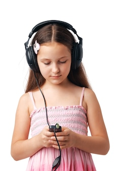 Jong meisje dat met hoofdtelefoons iets in haar mobiel of speler bekijkt