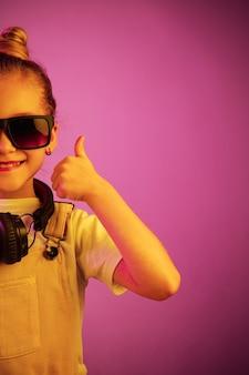 Jong meisje dat met hoofdtelefoons van muziek geniet