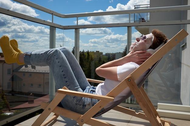 Jong meisje dat met leuk kapsel gezichtsmasker op gezicht toepast, muziek op hoofdtelefoons luistert en op het balkon zit.