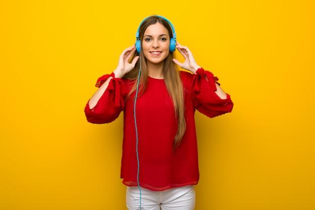 Jong meisje dat met rode kleding over gele muur aan muziek met hoofdtelefoons luistert