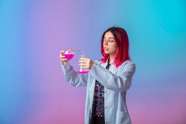 Jong meisje dat met roze haren chemische kolven houdt en reactie maakt.