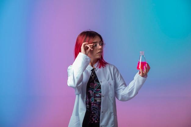 Jong meisje dat met roze haren een chemische kolf houdt en zorgvuldig kijkt.