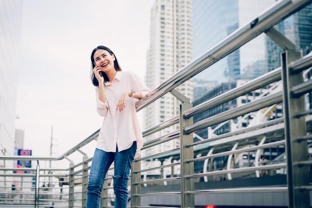 Jong meisje dat met smartphone en glimlach roept die op openlucht spreken. technologie concept.