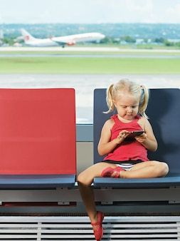 Jong meisje dat met telefoon in haar handen op vlucht op de luchthaven wacht