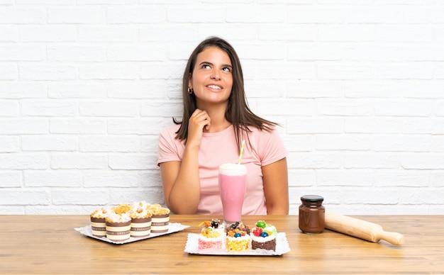 Jong meisje dat met veel verschillende minicakes een idee denkt