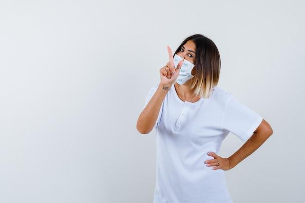 Jong meisje dat met wijsvinger benadrukt, hand op taille in wit t-shirt en masker houdt en er zelfverzekerd uitziet. vooraanzicht.
