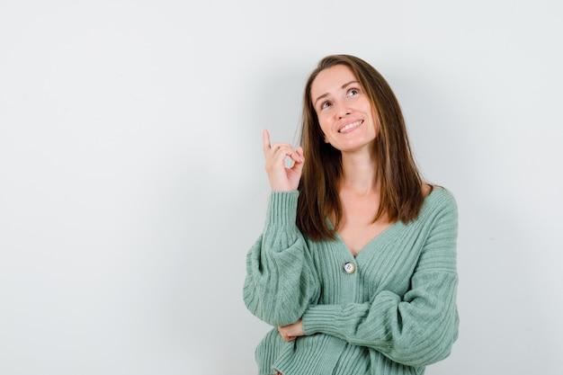 Jong meisje dat met wijsvinger benadrukt, omhoog kijkt in gebreide kleding, rok en gelukkig kijkt. vooraanzicht.