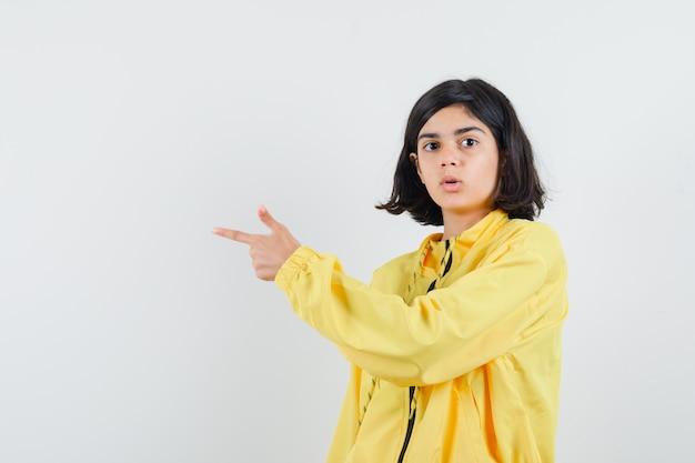 Jong meisje dat met wijsvingers in geel bomberjack naar links wijst en verbaasd kijkt.