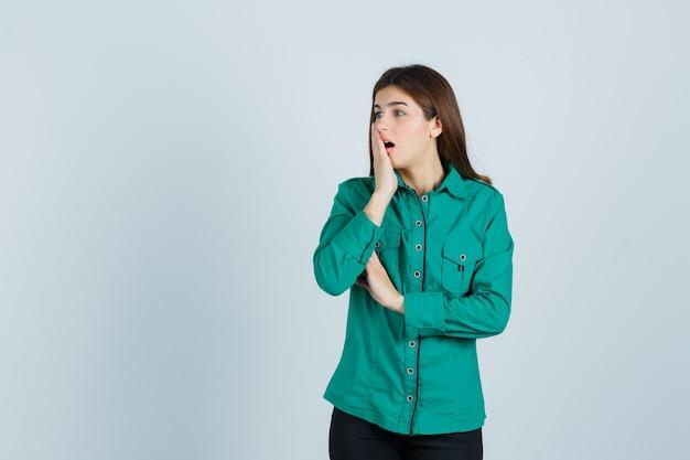 Jong meisje dat mond bedekt met hand, mond wijd open houdt in groene blouse, zwarte broek en geschokt kijkt. vooraanzicht.