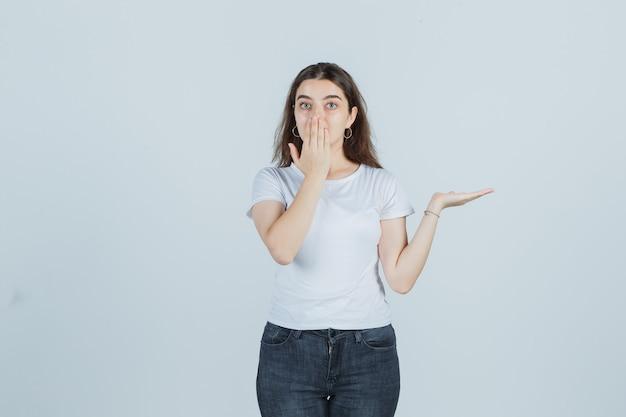 Jong meisje dat mond bedekt met hand, palm opzij spreidt in t-shirt, spijkerbroek en geschokt kijkt. vooraanzicht.
