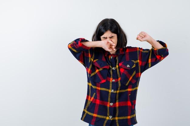 Jong meisje dat mond en neus bedekt met de hand terwijl ze zich uitstrekt in een geruit overhemd en er schattig uitziet, vooraanzicht.