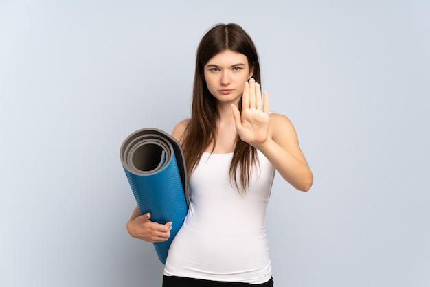Jong meisje dat naar yogalessen gaat terwijl het houden van een mat stopgebaar maakt