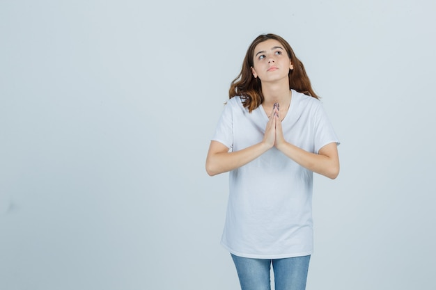 Jong meisje dat namaste gebaar in wit t-shirt toont en hoopvol, vooraanzicht kijkt.