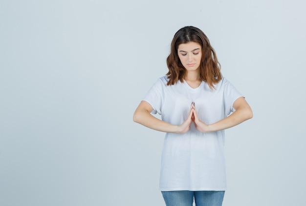 Jong meisje dat namaste gebaar in wit t-shirt toont en kalm, vooraanzicht kijkt.