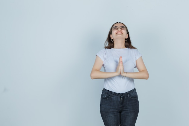 Jong meisje dat namaste-gebaar toont, omhoog in t-shirt, jeans kijkt en dankbaar kijkt. vooraanzicht.