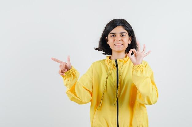 Jong meisje dat ok teken toont en links met wijsvinger in geel bomberjack wijst en optimistisch kijkt.