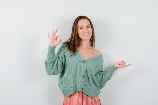 Jong meisje dat ok teken toont en met wijsvinger naar rechts in gebreide kleding, rok wijst en vrolijk kijkt. vooraanzicht.