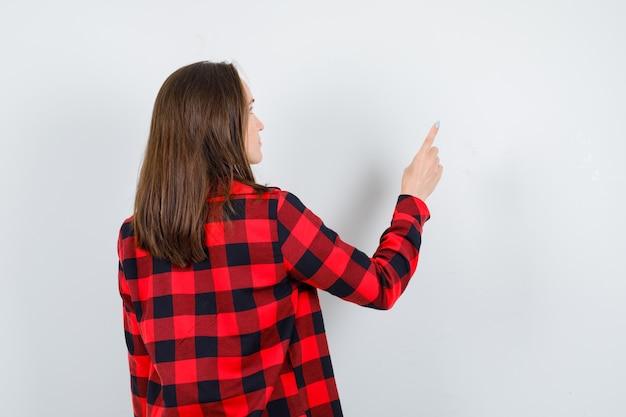 Jong meisje dat omhoog wijst in een geruit overhemd, blouse en er weemoedig uitziet, achteraanzicht.