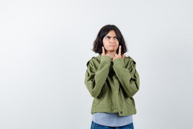 Jong meisje dat omhoog wijst in grijze trui, kaki jas, jeansbroek en peinzend kijkt. vooraanzicht.