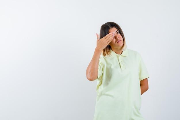 Jong meisje dat oog behandelt met hand, hand achter taille in t-shirt houdt en zelfverzekerd kijkt. vooraanzicht.