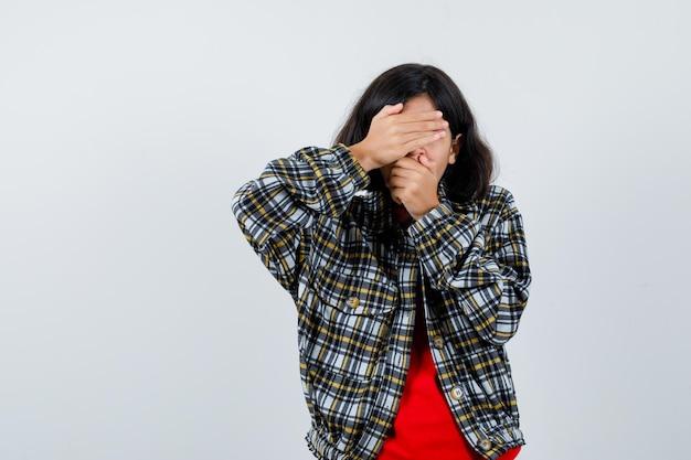 Jong meisje dat oog en mond bedekt met handen in geruit overhemd en rood t-shirt en er serieus uitziet, vooraanzicht.