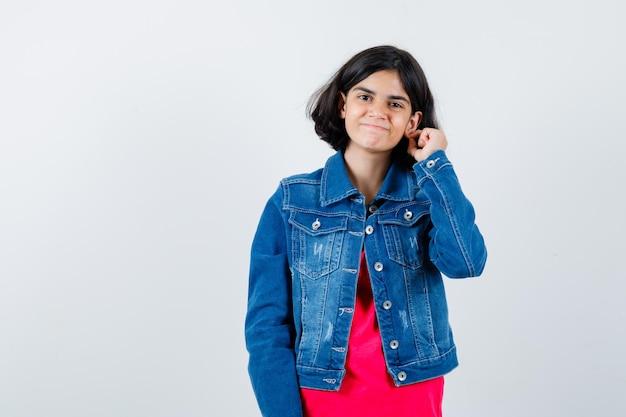 Jong meisje dat oor met vinger in rood t-shirt en jeansjasje uitrekt en vrolijk kijkt. vooraanzicht.