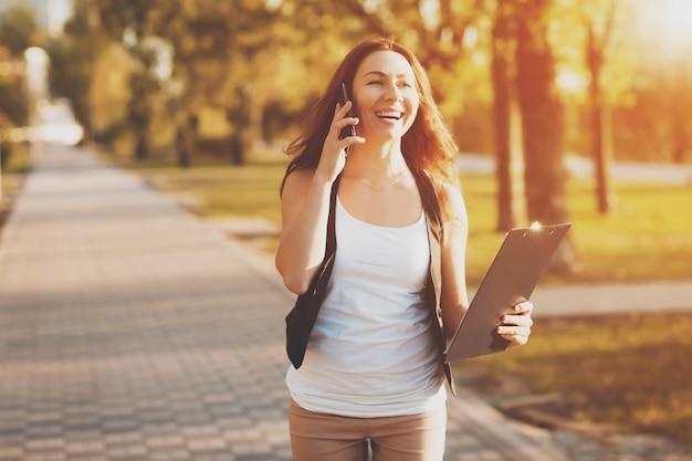 Jong meisje dat op een celtelefoon spreekt in het park