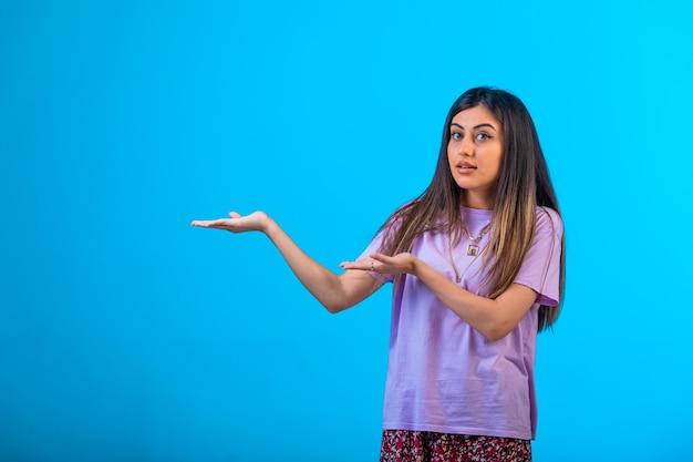 Jong meisje dat op iets op blauw richt.
