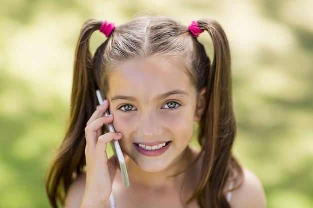 Jong meisje dat op mobiele telefoon spreekt