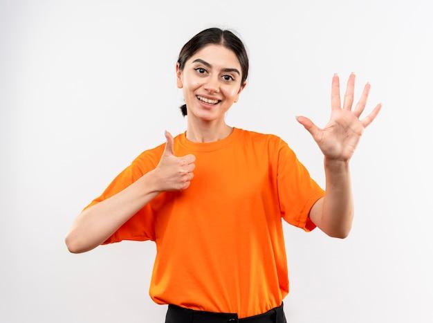Jong meisje dat oranje t-shirt draagt dat camera bekijkt die nummer zes toont die zich over witte achtergrond bevindt