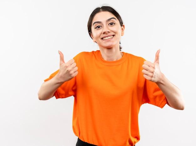 Jong meisje dat oranje t-shirt draagt dat met gelukkig gezicht glimlacht dat duimen toont die zich over witte muur bevinden