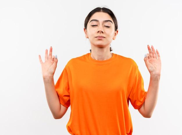 Jong meisje dat oranje t-shirt draagt dat met gesloten ogen ontspant die meditatiegebaar met vingers maakt die zich over witte muur bevinden